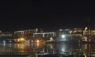 stadslandskap med silhuetter av hus och ljus från lyktor. foto
