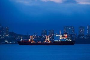 nattlandskap med havet och fartyg på bakgrunden av staden. foto
