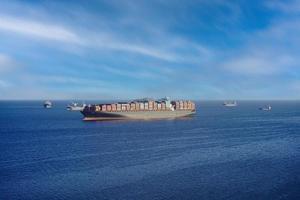 marinmålning med ett stort containerfartyg i horisonten. foto