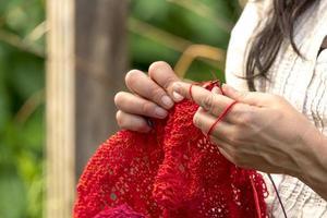 händer på en kvinna som virkar med röda ullstickor framför suddig bakgrund foto