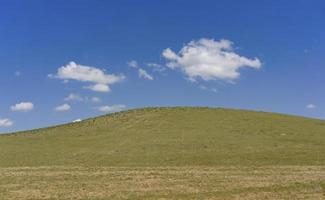 grön kulle täckt med gräs mot en blå himmel med moln. foto