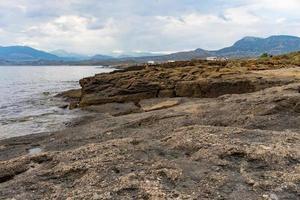 marinmålning med en stenig strandlinje under en blå himmel. foto