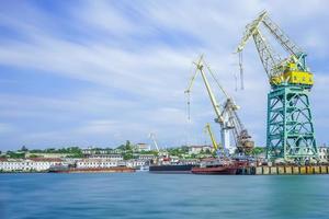 marinmålning med hamnens kust och stora flytande kranar. foto