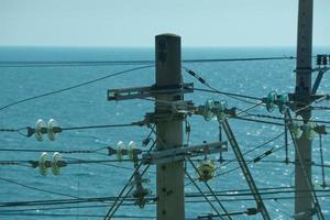 högspänningsledning mot det blå havet och klar himmel foto
