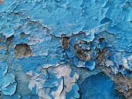 blå bakgrund med sprucken oljefärg på gips. foto