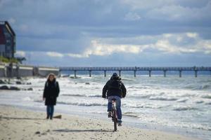 en äldre kvinna går längs sandstranden mot cyklisten. foto