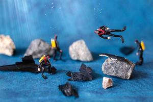 miniatyr människor, dykare rensar upp plastföroreningar som kasseras i havet, undervattensföroreningskoncept foto