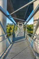 strandpromenad under en stor bro som korsar en flod foto