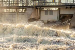 vatten som spolas från en öppen grind vid ett vattenkraftverk foto