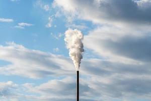rökstack högt upp i luften som förorenar atmosfären foto