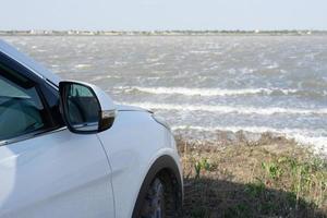 naturlandskap med en vit bil på stranden av en lera sjö. foto