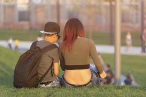 ung man och flicka sitter med ryggen på det gröna gräset. foto