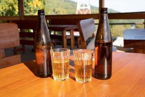 flaskor och glas med saft på ett träbord foto