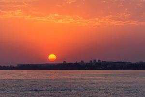 ljus solnedgång över ett lugnt hav och färgglad himmel foto