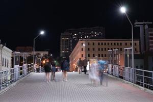 nattlandskap med människor på bron till järnvägsstationen. foto