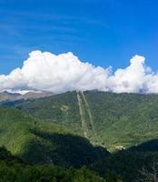 vackra bergslandskap på blå himmel bakgrund med moln foto