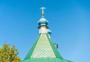 taket på klostret med ett gyllene kors mot den blå himlen. foto