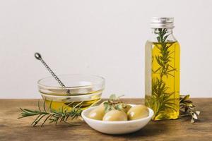 olivolja flaska med rosmarin oliver. vackert fotokoncept med hög kvalitet och upplösning foto