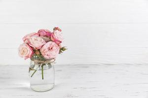 rosa rosor i blommaglasburk på vit trä texturerat bakgrund foto