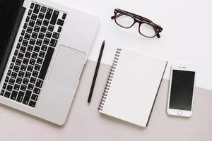 anteckningsblock och glasögon med laptop och smartphone layout foto