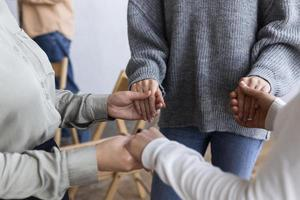 människor som håller hand i gruppterapisession foto