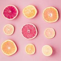 skivor av färska citrusfrukter på rosa bakgrund foto