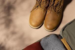 öppnat bagage med vikta kläder och skor foto