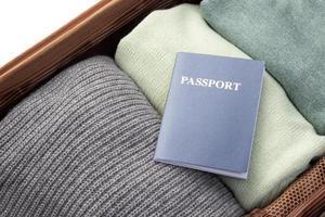 öppnat bagage med vikta kläder och pass foto