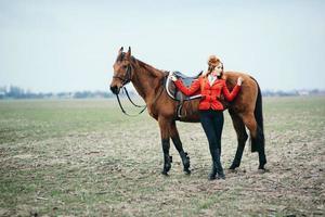 rödhårig jockeytjej i en röd kofta och svarta höga stövlar med en häst foto