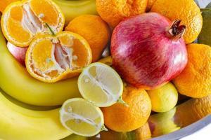 diverse fruktarrangemang av bananer, granatäpple, skivad citron och skivad mandarin foto