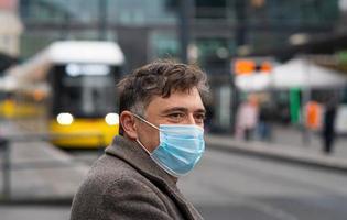 bär skyddande masker utomhus i staden foto