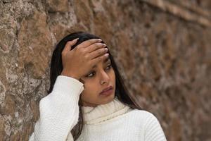närbild porträtt av en trött brunett kvinna med en hand i pannan foto