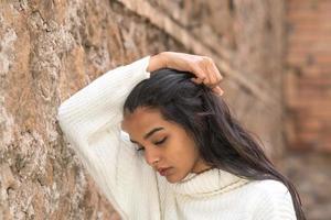 porträtt av en romantisk brunettkvinna med handen i håret som ser bort foto