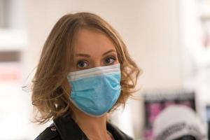 ung kvinna som bär en medicinsk mask foto
