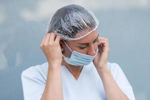 kvinnadoktor som tar på sig ansiktsmasken foto