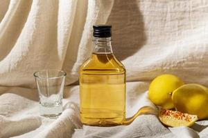 mezcal eller tequila i en flaska med neutral linnebakgrund foto
