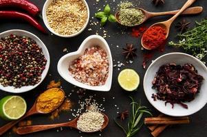 färgglada och aromatiska örter och kryddor på en mörk bakgrund foto