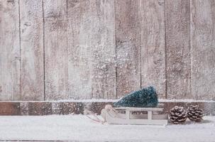 trävägg med liten släde med julgran. vackert fotokoncept med hög kvalitet och upplösning foto