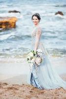 brud med en bukett blommor på stranden foto