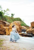 brud i en blå ljus klänning som går längs havet foto
