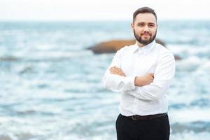 brudgummen i en vit skjorta och svarta byxor vid havet foto
