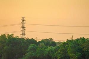 högspänning el torn och kabel med orange himmel solnedgång bakgrund, landskap av tropisk skog foto