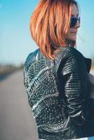 rödhårig flicka i en svart jacka och blå glasögon foto