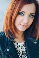 rödhårig flicka i en svart jacka och blå ögon foto