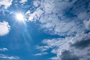 vacker vit sol och moln på blå himmel foto