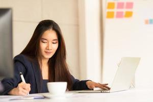 asiatisk affärskvinna som arbetar på bärbar dator foto