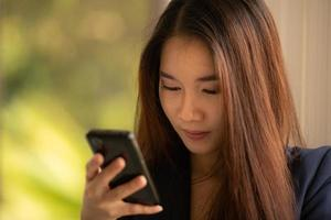 asiatisk affärskvinna som använder mobiltelefonen på ett kontor foto