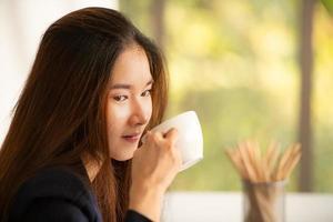 asiatisk affärskvinna som dricker kaffe på ett kontor foto