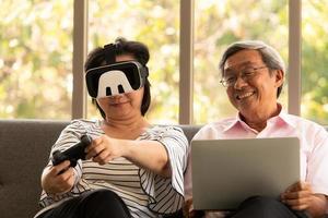senior asiatisk man och kvinna kopplar av på semester i den naturliga vardagsrumsbakgrunden med modern teknik foto