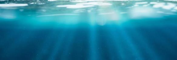 blå under vattnet med solljus som skiner genom vattenytan i tropiska havet foto